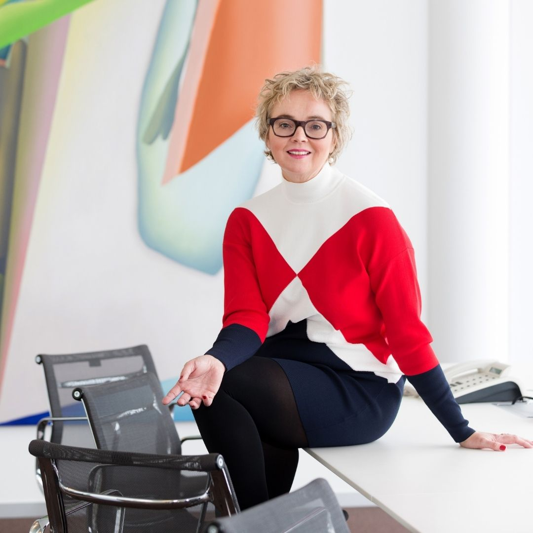 Christine von Fragstein sitzt auf einem Schreibtisch